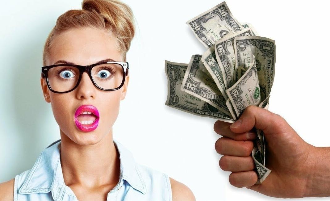 Удивленная девушка в очках и долларовые купюры в мужской руке