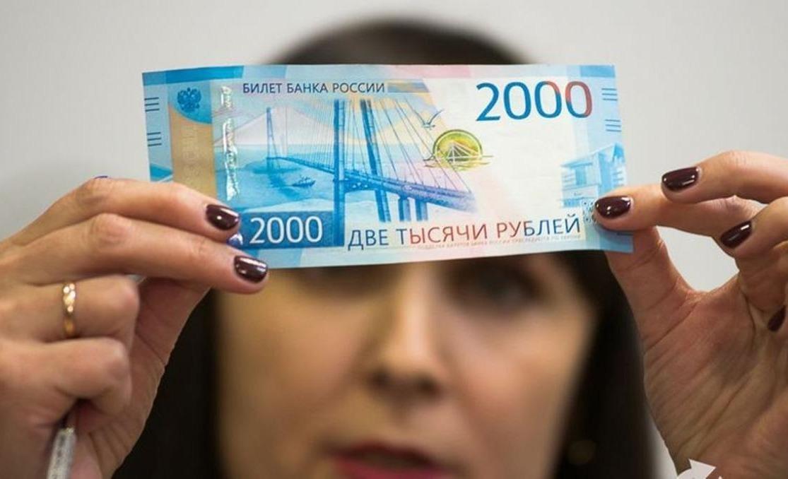 Женщина изучает 2-тысячную рублевую купюру