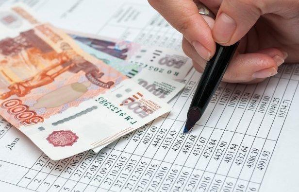 Деньги, таблица с цифрами и рука с ручкой