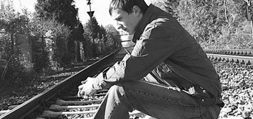 парень сидит на рельсах