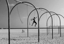 мужик на кольцах Спорт на пляже в Санта-Монике